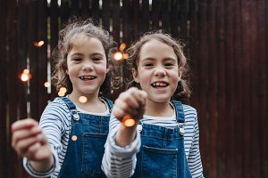 Girls joyfully holding sparklers