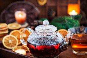 Glass teapot of hot black tea on coz