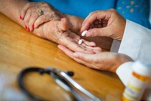 Doctor Hands Senior Adult Woman Meds