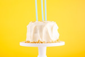 Birthday cake with candles on yellow