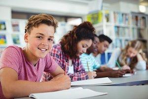 Portrait of happy schoolboy studying