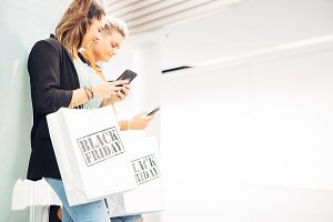 Female shoppers using mobile phone