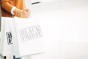 Woman holds black friday shopping ba