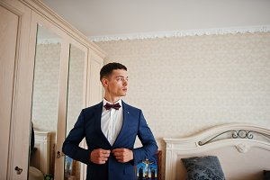 Handsome groom dressing up and getti