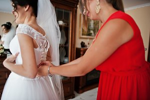 Bridesmaid helping to tie a ribbon o