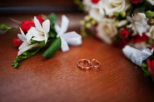 Wedding rings with bouquet and butto