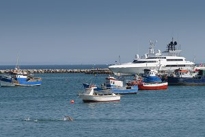 Fishing boats and luxury yacht