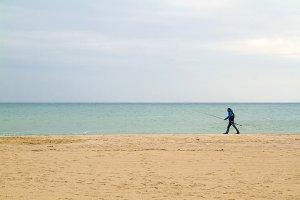 Fisherman walking in the beach
