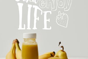 yellow detox smoothie in bottles wit