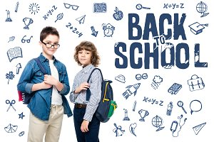 two schoolboys with backpacks lookin