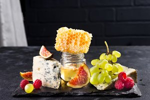 Grape, cheese, figs and honey on a