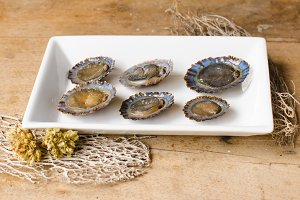 Raw limpets, rustic background.