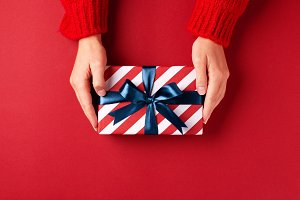 Hands holding striped gift box.