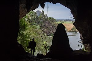 Cave with man standing on a rock in