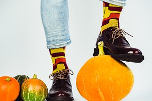 Beautiful pumpkins and men's legs in