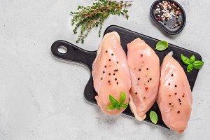 Raw chicken breast with fresh basil