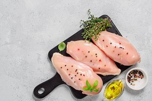 Raw chicken breast with fresh basil