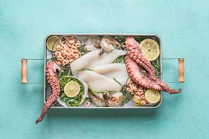 Various seafood in tray on blue