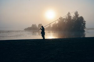 Silhouette of fisherman fishing with
