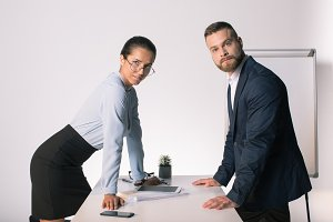 Confident young business people lean