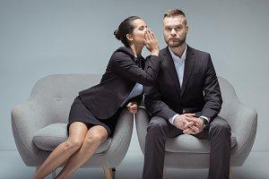 businesswoman whispering something o