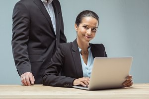 smiling businesswoman typing on lapt