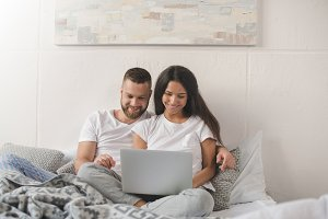 smiling young couple using laptop wh