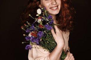 cheerful elegant redhead girl holdin