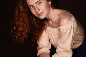 tender redhead woman posing in beige