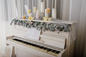 White piano with candles. Happy wint