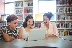 Happy students using laptop