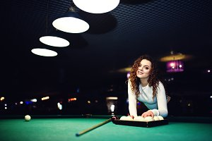 Young curly girl posed near billiard