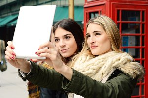 Two young girlfriends taking selfie