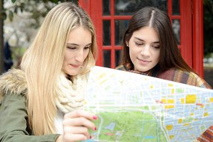 Two young tourists looking at a map.