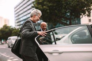 Happy businessman getting into a cab