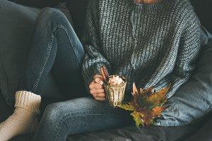 Woman in woolen sweater holding mug
