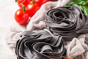 Black uncooked pasta  with tomato an
