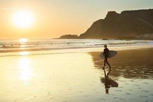 woman surfboard walk beach Portugal