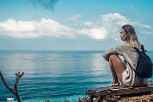 girl sits over the blue ocean