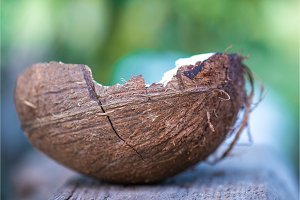 half coconut rests on a wooden