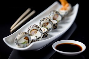Sushi rolls on white plate. Black