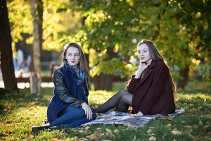 Two beautiful girls in coats sit on