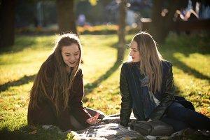 Two pretty girls in coats talking