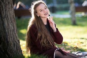 Girl in coat smiling sitting on a