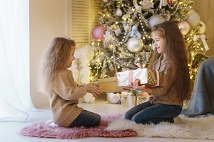Two little sisters at Christmas tree