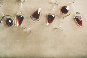 Red wine in glasses over grey