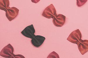 Pink and black pasta farfalle lies