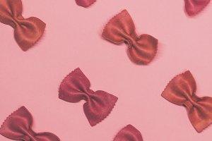 Pink pasta farfalle lies diagonally