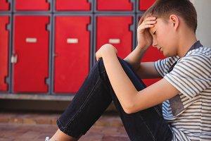 Sad schoolboy sitting on staircase