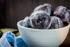 Plums in a pottery bowl on dark rust